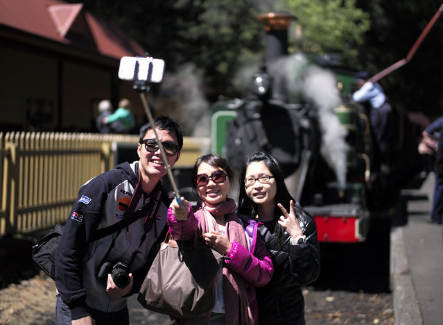 "Tourists take a ""selfie"" picture in front of Puffing Billy steam engine 6A during a water stop at Lakeside station near Melbourne, October 20, 2014. While the discovery of steam power 200 years ago powered the Industrial Revolution, the world long ago shunted most steam trains onto the sidings of history. (Photo by Jason Reed/Reuters)"