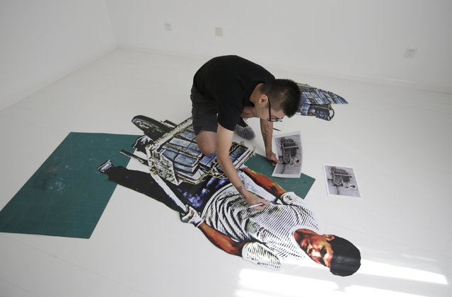 Chinese artist ROBBBB works on an art piece depicting a construction worker, in his studio in Beijing October 1, 2015. (Photo by Jason Lee/Reuters)