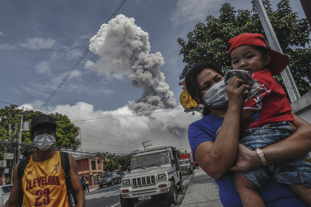 A woman covers the face of a child as Mount Mayon spews a huge column of ash noon in Camalig, Albay province, Philippines, January 24, 2018. (Photo by Ezra Acayan/NurPhoto via Getty Images)