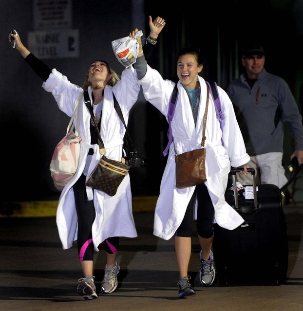 Kendall Jenkins, left, celebrates with a friend after getting off the Carnival Triumph in Mobile, Alabama, February 14, 2013. The ship with more than 4,200 passengers and crew members has been idled for nearly a week in the Gulf of Mexico following an engine room fire. (Photo by John David Mercer/Associated Press)