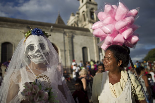 A street vendor, right, looks at a disguised reveler during celebrations marking the 9th International Poetry Festival honoring Nicaraguan poet, priest and former Nicaragua's Culture Minister, Ernesto Cardenal, not in picture, in Granada, Nicaragua, Wednesday, Feb 20, 2013. The festival is attended by more than 300 poets from some 60 countries. (Photo by Esteban Felix/AP Photo)