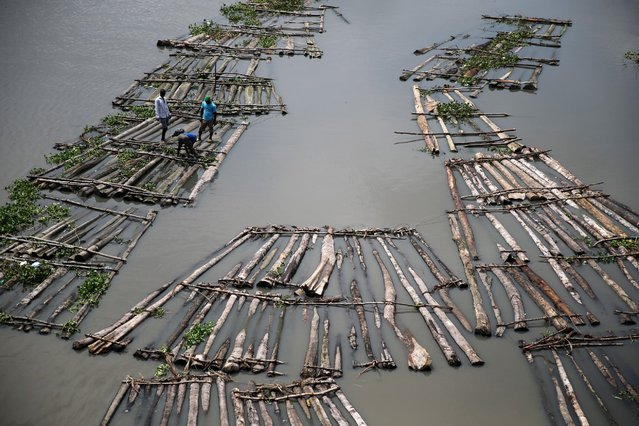 Men stand on a raft near the Okobaba sawmill at the edge of the Lagos Lagoon September 25, 2014. (Photo by Akintunde Akinleye/Reuters)