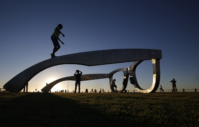 """Youths pose for photographs as they climb on top of a sculpture in the form of a giant pair of spectacles on Cape Town's Sea Point Promenade, November 18, 2014. Inspired by Nelson Mandela, the work """"Perceiving Freedom"""" by artist Michael Elion has stirred some controversy in the local media. While popular with visitors to the promenade, some critics have questioned the association of Mandela's legacy with commercial sponsors. (Photo by Mike Hutchings/Reuters)"""
