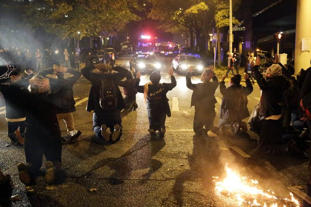 Protesters get down on their knees during a demonstration following the grand jury decision in the Ferguson, Missouri shooting of Michael Brown, in Seattle, Washington November 24, 2014. (Photo by Jason Redmond/Reuters)
