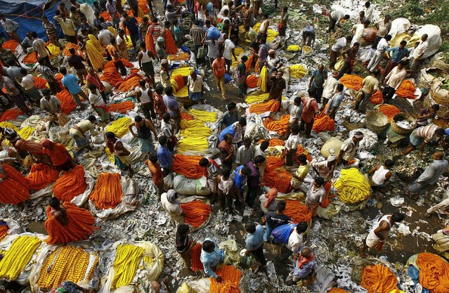 Vendors sell garlands of marigold flowers at a wholesale flower market during Durga Puja festival in Kolkata October 20, 2015. (Photo by Rupak De Chowdhuri/Reuters)