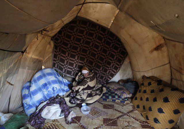 Um Mohamed, a 87-year-old displaced woman, sits inside a tent that was erected atop of an archaeological hill in Jabal al-Zawiya in the southern countryside of Idlib November 26, 2014. (Photo by Khalil Ashawi/Reuters)