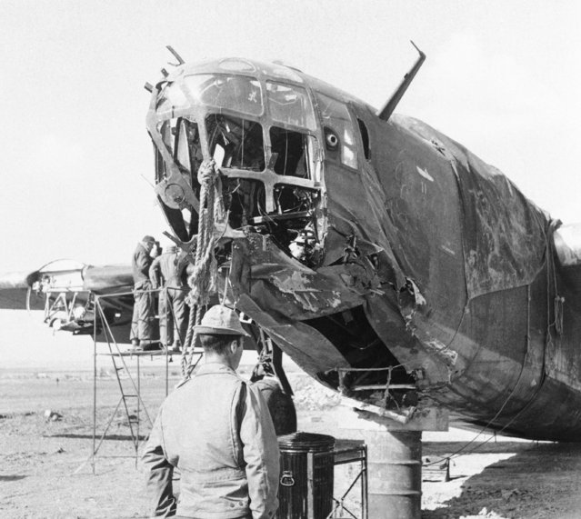 U.S. Army bomber made her way back to her advanced base in Tunisia, January 4, 1943 in spite of severe damaged absorbed during a raid on the Tunisian front in support of ground troops advancing against Rommel's forces. The service unit rushes repairs to get the plane in action against the axis in a day of two. (Photo by AP Photo)