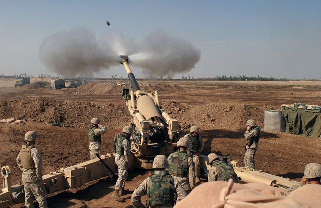 A Howitzer gun crew of 4th Battalion, 14th Marines, Mike Battery, Gun 4, engage enemy targets during the Second Battle of Fallujah, on November 11, 2004. (Photo by Lance Corporal Samantha L. Jones/USMC/The Atlantic)