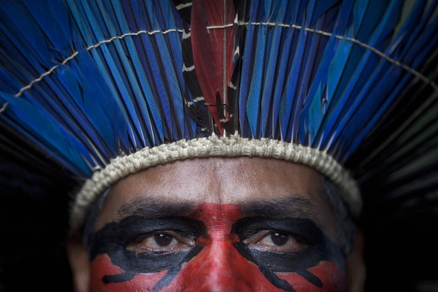 An indigenous man wearing face paint and a headdress stands inside the abandoned old Indian museum in Rio de Janeiro, Brazil, Thursday, March 21, 2013. Brazilian Federal Court ruled that indigenous people who have been occupying the building since 2006 have to leave the area because it is next to the Maracana stadium, which will be the site of the final match of the 2014 World Cup soccer tournament and the opening and closing ceremonies of the 2016 Olympic games. Authorities say the compound must go as the area around the stadium is being transformed into a shopping and sports entertainment hub. (Photo by Felipe Dana/AP Photo)