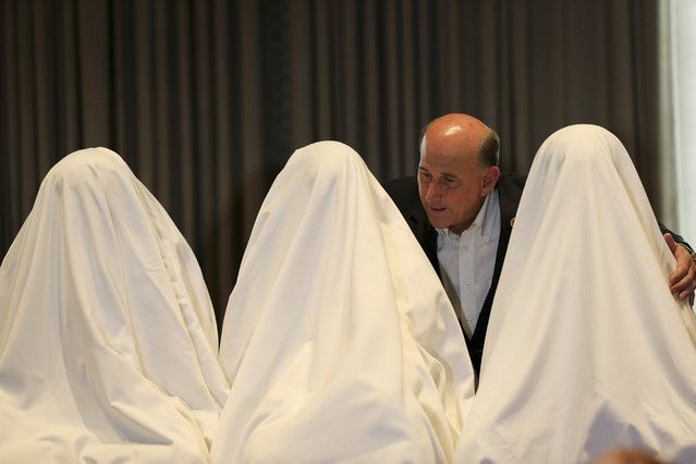 U.S. congressman Louie Gohmert speaks with three girls covered in white sheets, who escaped after being abducted in the remote village of Chibok, during a news conference in Lagos, in this June 5, 2014 file photo. (Photo by Akintunde Akinleye/Reuters)