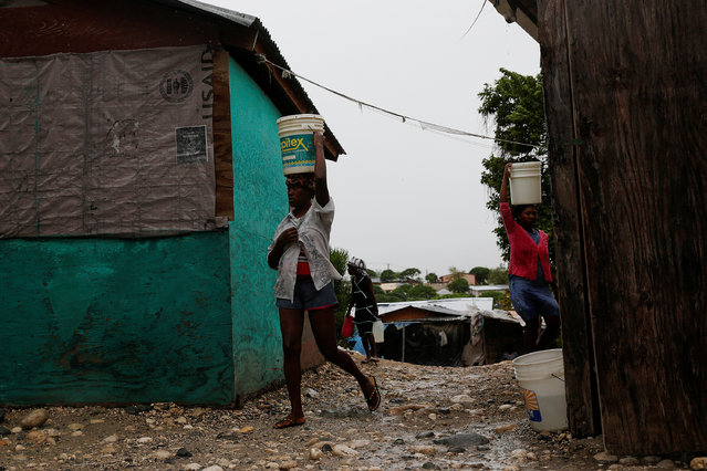Women carry plastic containers at a camp for displaced people while Hurricane Matthew approaches in Port-au-Prince, Haiti October 3, 2016. (Photo by Carlos Garcia Rawlins/Reuters)