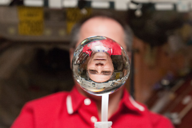 NASA astronaut Kevin Ford, Expedition 34 commander, watches a water bubble float freely between him and the camera, showing his image refracted, in the Unity node of the ISS, on January 30, 2013. (Photo by Reuters/NASA/The Atlantic)