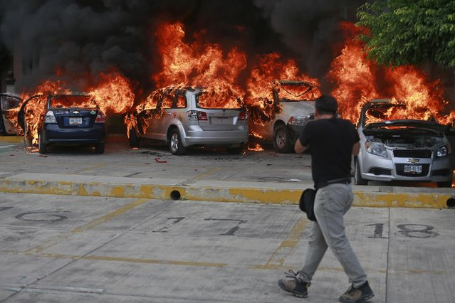 A news photographer take pictures of cars set alight by CETEG (State Coordinator of Teachers of Guerrero teacher's union) members at a City Congress parking lot in Chilpancingo, November 12, 2014. (Photo by Jorge Dan Lopez/Reuters)