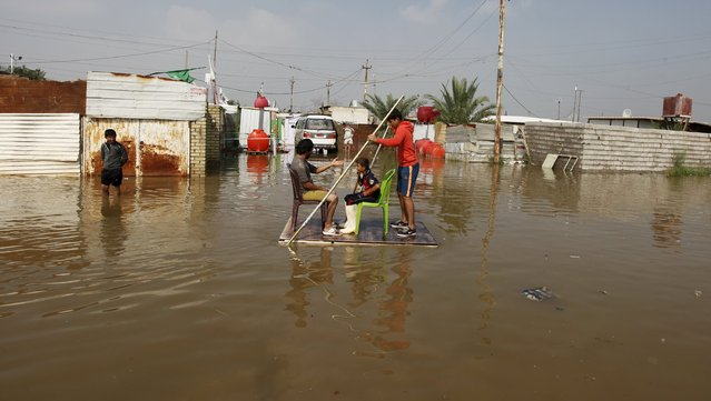 People use a board to travel on a flooded street after heavy rainfall in Baghdad, Iraq, October 31 2015. (Photo by Ahmed Saad/Reuters)