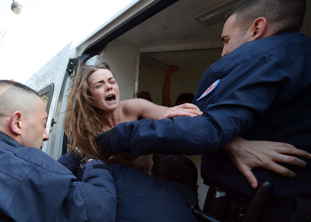 """An activist of the women's rights movement Femen is expelled by the police during a topless protest near Tunisia's Embassy in Paris on April 4, 2013. Femen called for a day of international """"topless jihad"""" on April 4 with Femen groups staging protests in various European cities in support of Amina, a young Tunisian woman who caused a scandal when she published photos of herself bare-chested on the internet in March. (Photo by Miguel Medina/AFP Photo)"""