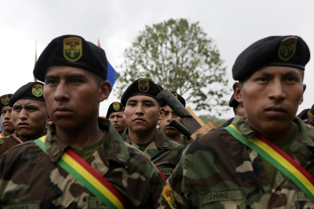 Soldiers, who were tasked to eradicate coca leaves in the fight against drugs, attend the end of their ceremony of the task in Chimore, east of La Paz, December 10, 2014. (Photo by David Mercado/Reuters)