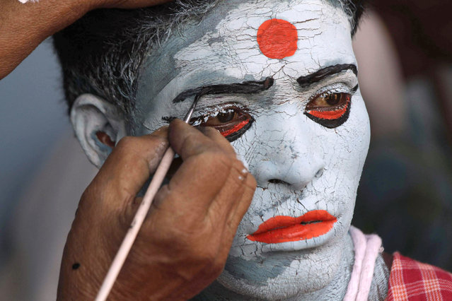 An artist paints the face of a devotee during Shiva Gajan Hindu festival celebrations in Kurmun, about 120 kilometers (75 miles) from Kolkata, India, Friday, April 12, 2013. Faithful Hindu devotees offer various rituals each year in hope of winning the favor of Hindu God Shiva and ensuring the fulfillment of their wishes. (Photo by Bikas Das/AP Photo)
