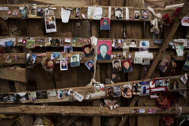 Pictures of missing people are placed on the wall near a monastery above the Larung Wuming Buddhist Institute, located some 3700 to 4000 metres above the sea level in remote Sertar county, Garze Tibetan Autonomous Prefecture, Sichuan province, China October 30, 2015. According to local people, placing photos of those missing near screed places in the valley can help relatives find their loved ones. (Photo by Damir Sagolj/Reuters)