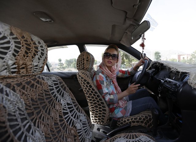Kanaz, 21, listens to her instructor (unseen) during a practical driving lesson in Kabul August 14, 2014. (Photo by Mohammad Ismail/Reuters)