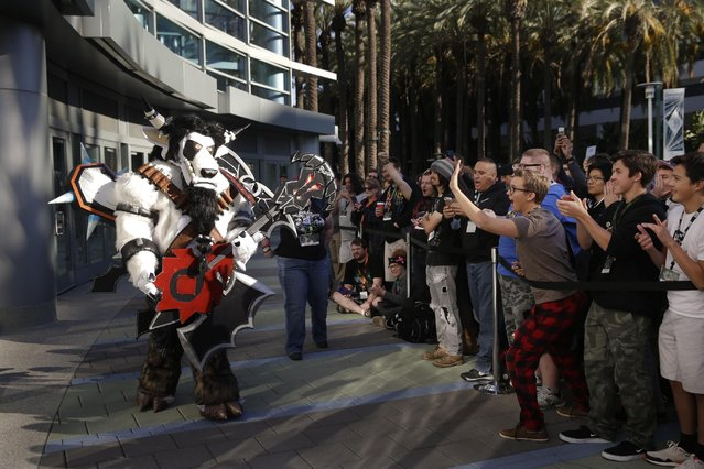 "A man dressed as a video game character walks past people waiting in line to attend the BlizzCon, Friday, November 6, 2015, in Anaheim, Calif. ""World of Warcraft"" maker Blizzard is hosting its ninth annual fan-centric convention opening Friday. (Photo by Jae C. Hong/AP Photo)"