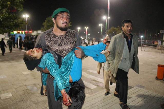 This photograph taken late on October 11, 2016 shows an Afghan man carrying a wounded girl after an attack by gunmen at the Karte Sakhi shrine in Kabul. Grieving worshippers on October 12 described desperately trying to shelter their children against a hail of gunfire in Kabul that killed at least 18 people gathering to mark Ashura, one of the most important festivals of the Shiite calendar. (Photo by Rohullah Amin/AFP Photo)