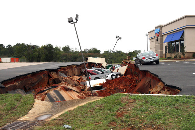 This photo shows vehicles after a cave-in of a restaurant parking lot in Meridian, Miss., Sunday, November 8, 2015. Experts are to begin work Monday seeking to determine the cause of the Saturday collapse, authorities said. (Photo by Michael Stewart/The Meridian Star via AP Photo)