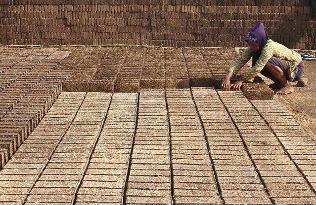 A worker makes bricks at Boja village in Kendal, in this December 22, 2014 picture taken by Antara Foto. (Photo by Aditya Pradana/Reuters/Antara Foto)