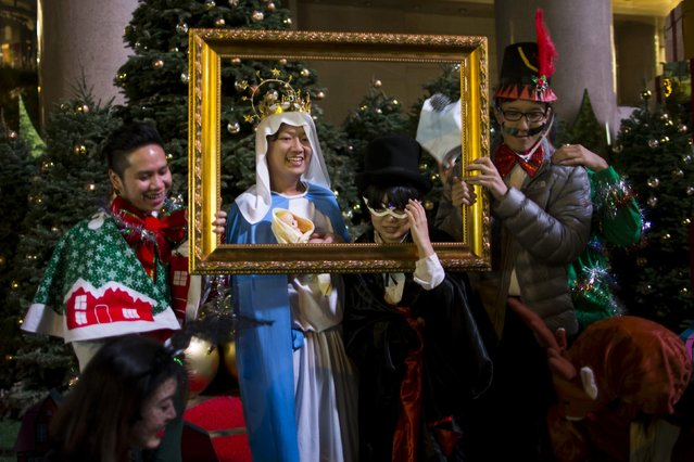People wearing costumes pose for a photo as they celebrate Christmas at Times Square in Hong Kong early December 25, 2014. (Photo by Tyrone Siu/Reuters)