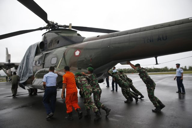 Military personnel move an Indonesian military helicopter used in recovery efforts for the missing AirAsia plane, as it sits idle due to bad weather, on the tarmac of Iskandar Airport in Pangkalan Bun, Central Kalimantan, December 31, 2014. (Photo by Darren Whiteside/Reuters)