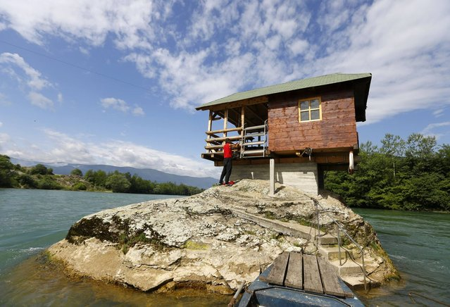 A man enters a house built on a rock on the river Drina near the western Serbian town of Bajina Basta, about 160km (99 miles) from the capital Belgrade May 22, 2013. (Photo by Marko Djurica/Reuters)