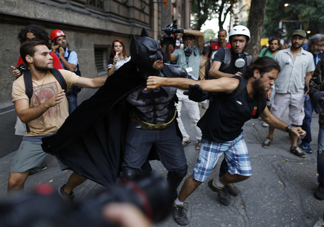 A man wearing a Batman costume reacts after being punched in the face during a protest against the increase in bus fares, in Rio de Janeiro, Brazil, Friday, January 9, 2015. He was attacked after being accused by several demonstrators of having participated in political rallies against the Workers Party during the electoral campaign. (Photo by Leo Correa/AP Photo)