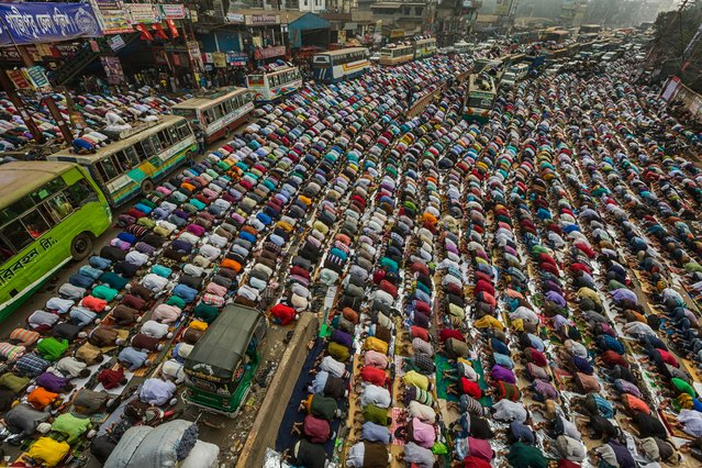"""""""Prayers on the road"""". Devotees praying on the Dhaka-Mymensingh highway, Bangladesh, on first day of Bishwa Ijtema, the second largest Islamic congregation after the Hajj, organised on the banks of the Turag river. Honourable mention: Travel. (Photo by Muhammad Mostafigur Rahman/SIPA Contest)"""