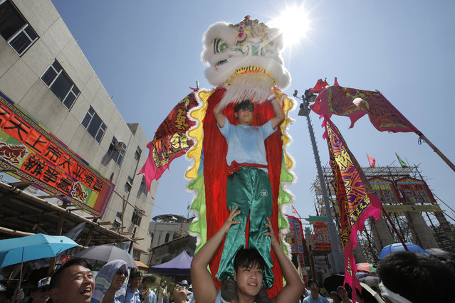Villagers perform lion dance during a parade on the outlying Cheung Chau island in Hong Kong to celebrate the Bun Festival Tuesday, May 22, 2018. (Photo by Kin Cheung/AP Photo)
