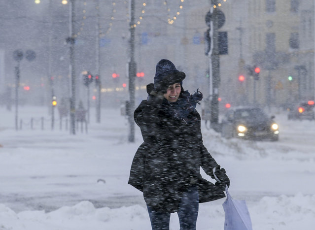 A woman struggles to walk along a street with thick layer of snow in Helsinki, Finland, making all kinds of travel difficult on Tuesday January 12, 2021. The heavy snowfall is predicted to continue until Wednesday in Southern Finland. (Photo by Markku Ulander/Lehtikuva via AP Photo)