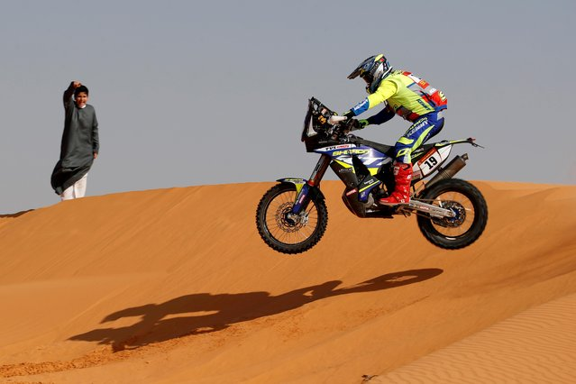 Sherco Factory's Rui Goncalves in action during stage 6 as a boy cheers, Al Qaisumah to Ha'il, Saudi Arabia on January 8, 2021. (Photo by Hamad I Mohammed/Reuters)
