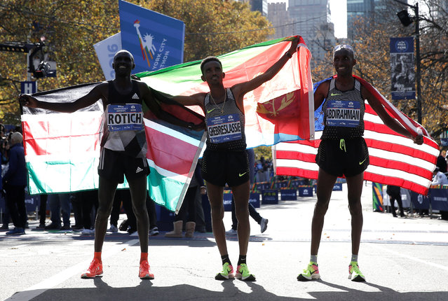 Winner Ghirmay Ghebreslassie of Eritrea (C), 2nd place finisher Lucas Rotich of Kenya (L) and third place finisher Abdi Abdirahman of the U.S. (R) pose together at the finish line of the 2016 New York City Marathon in Central Park in the Manhattan borough of New York City, NY, U.S. November 6, 2016. (Photo by Mike Segar/Reuters)