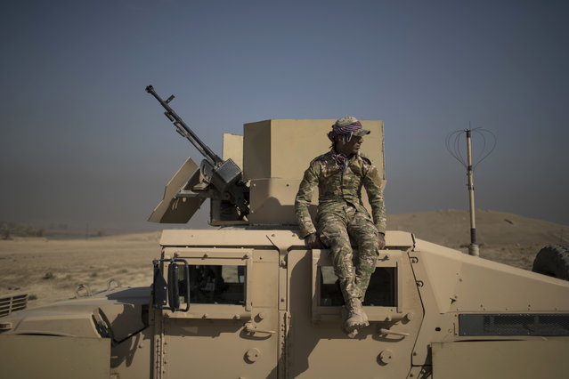 An Iraqi army soldier sits atop an armored vehicle on the outskirts of Hamam al-Alil, south of Mosul, Iraq, Sunday, November 6, 2016. On the southern front, Iraqi forces are still some 12 miles (20 kilometers) from the city center. The fighting is centered on the town of Hamam al-Alil, where Associated Press journalists could hear gunfire and saw attack helicopters firing on IS positions. (Photo by Felipe Dana/AP Photo)