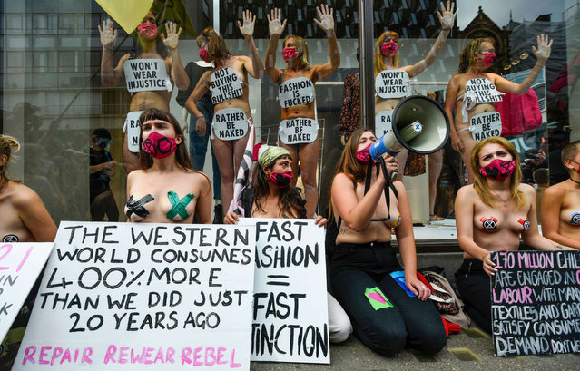 """Activists from Extinction Rebellion (XR) stage a """"Guerilla Repair"""" pop-up outside the H&M store on Oxford Street in London, England on September 9, 2020 to protest against the environmental and human effects of fast fashion and disposable fashion. Some are have glued their hands to the inside of the shop window. (Photo byStephen Chung/LNP/Rex Features/Shutterstock)"""