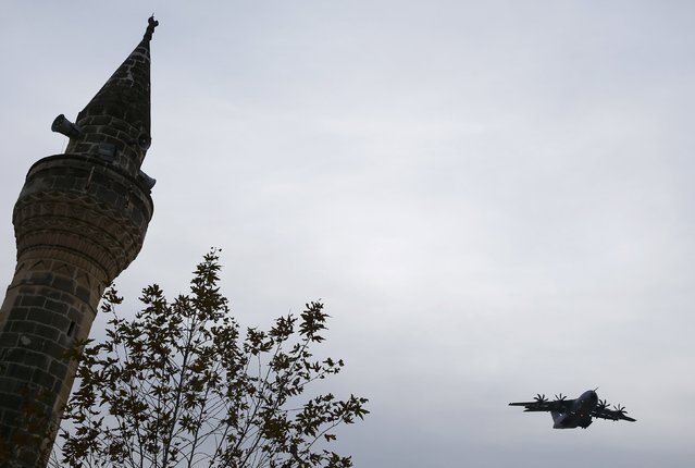 A German airforce Airbus A400M military refuelling aircraft flies past a minoret shortly before the landing at an airbase in Incirlik, Turkey, December 10, 2015. (Photo by Umit Bektas/Reuters)