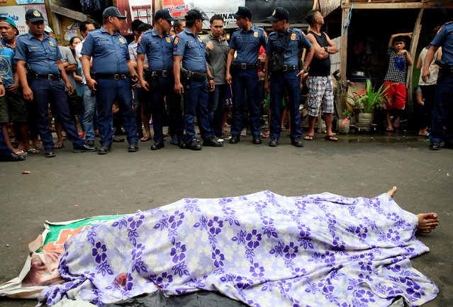 Members of the Philippine National Police (PNP) gather in front of the body of what the local police said was a suspected drug pusher, who was killed with other suspected drug pushers in a gunfight with local police during an anti-illegal drug operation, in metro Manila, Philippines November 10, 2016. (Photo by Romeo Ranoco/Reuters)