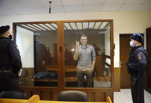 Opposition leader Alexei Navalny stands in a cage in the Babuskinsky District Court in Moscow, Russia, Saturday, February 20, 2021. Two trials against Navalny are being held Moscow City Court one considering an appeal against his imprisonment in the embezzlement case and another announcing a verdict in the defamation case. (Photo by Alexander Zemlianichenko/AP Photo)