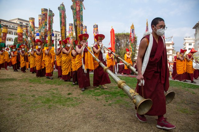 Nepalese Buddhist monks play traditional instruments during a procession after the body of Tsikey Chokling Rinpoche, arrived at the Ka-Nying Shedrub Ling monastery in Kathmandu, Nepal, Sunday, January 17, 2021. The Tibetan Buddhist religious teacher died in Singapore on Dec 18, 2020. (Photo by Niranjan Shrestha/AP Photo)