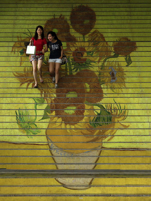 "Shoppers walk down stairs featuring a five-metre-high reproduction of Vincent van Gogh's signature painting ""Sunflowers"", at the entrance to Ocean Terminal in Hong Kong July 15, 2013. A premium three-dimensional reproduction of works of Van Gogh, the RELIEVO collection, approved by the curators of the Van Gogh Museum in Amsterdam, is on display at a gallery inside Harbour City shopping mall attached to the terminal. (Photo by Bobby Yip/Reuters)"