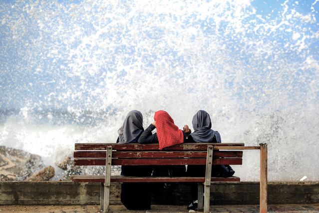 Three Palestinian women sit on a beachfront as a wave comes rushing by in Gaza City on November 17, 2016. (Photo by Mohammed Abed/AFP Photo)