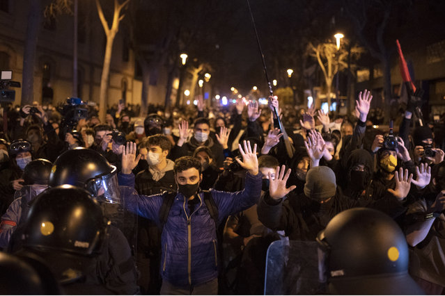 Demonstrators react as police cordon off the street during a march in Barcelona, Spain, Saturday, March 6, 2021. Several hundred protesters are marching in northeastern Spain's Barcelona against the crackdown that has followed the recent violent outcry over the imprisonment of Pablo Hasél, an outspoken anti-establishment artist and activist. (Photo by Emilio Morenatti/AP Photo)