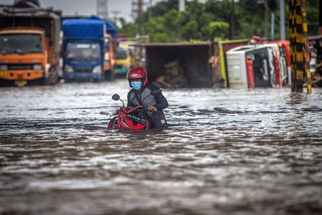 A resident pushes their motorbike through flood waters caused by torrential rain in Semarang, central Java, Indonesia on February 23, 2021. (Photo by W.F. Sihardian/NurPhoto/Rex Features/Shutterstock)