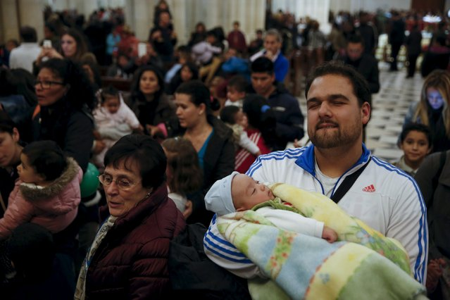 People wait in line to have a picture of their children taken on the lap of one of the Three Wise Men during a distribution of free toys for low-income families at Almudena Cathedral in Madrid, Spain, December 22, 2015. (Photo by Susana Vera/Reuters)