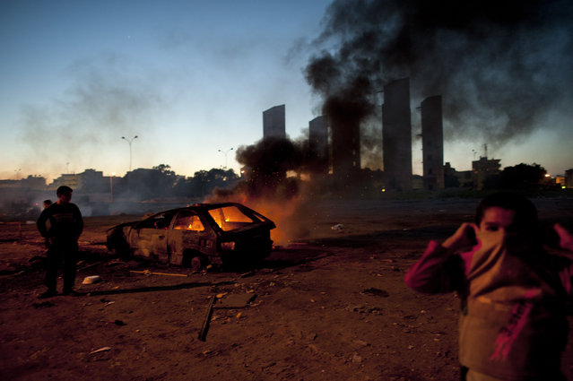 Kids play around a burning car in a residential neighborhood in Benghazi, in Eastern Libya, February 28, 2011. (Photo by Lynsey Addario/The New York Times)