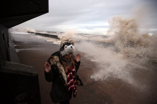 A girl runs from waves crashing over the promenade on December 24, 2015 in Blackpool, England. The Met Office is warning of 80mph winds and torrential downpours over the Christmas holidays, as dozens of flood alerts are issued for already devastated regions. (Photo by Nigel Roddis/Getty Images)