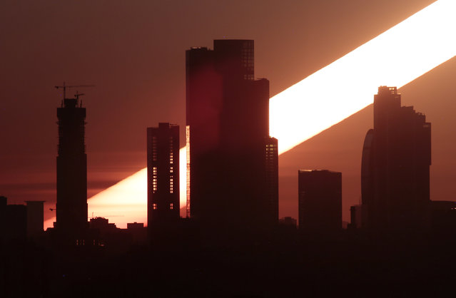 """The sun rises behind the skyscrapers of the Moscow International Business Centre, also known as """"Moskva-City"""", in Moscow, Russia April 23, 2018. (Photo by Anton Vaganov/Reuters)"""